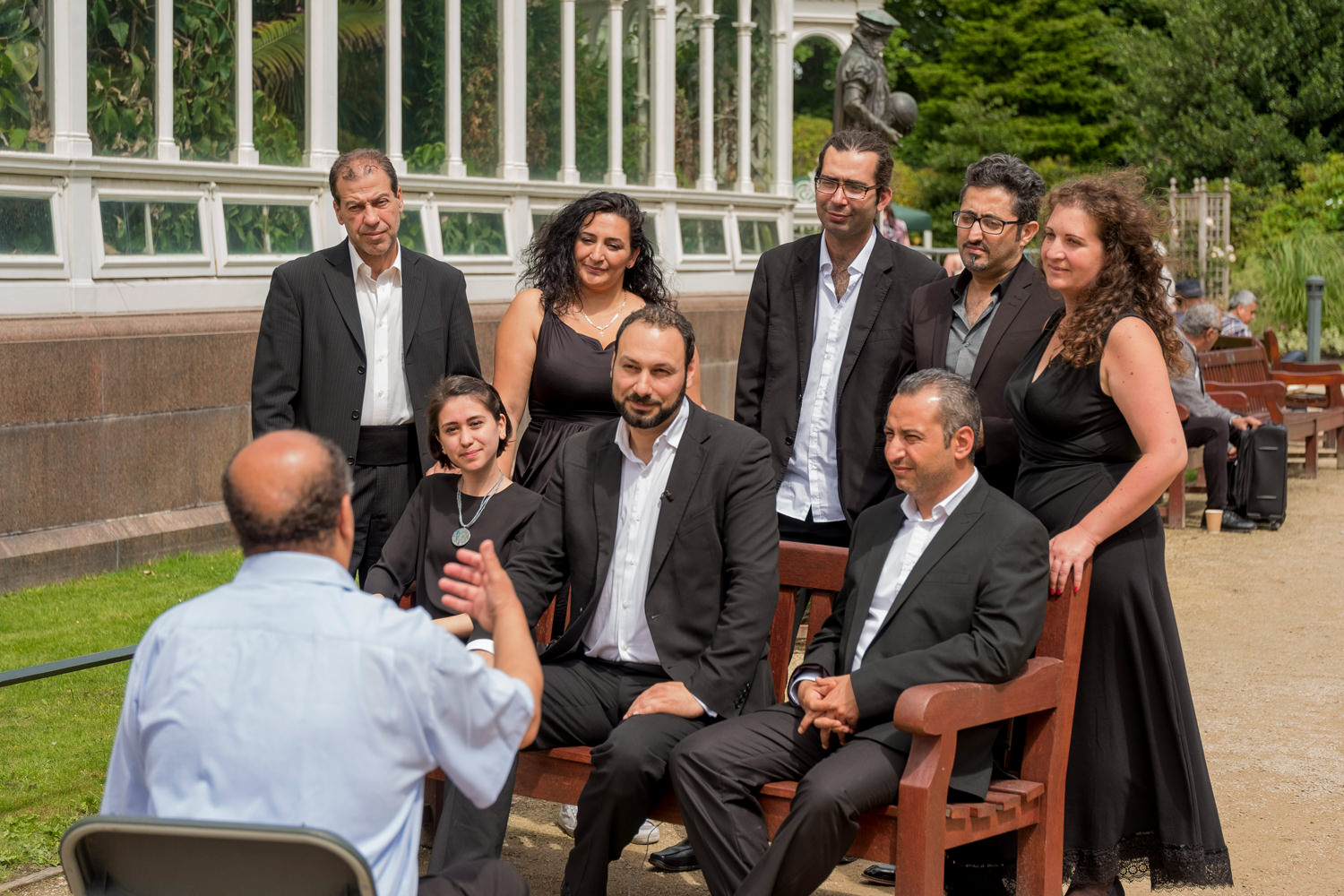 A group of men and women in smart, black clothes with a man sitting on a chair talking to them.