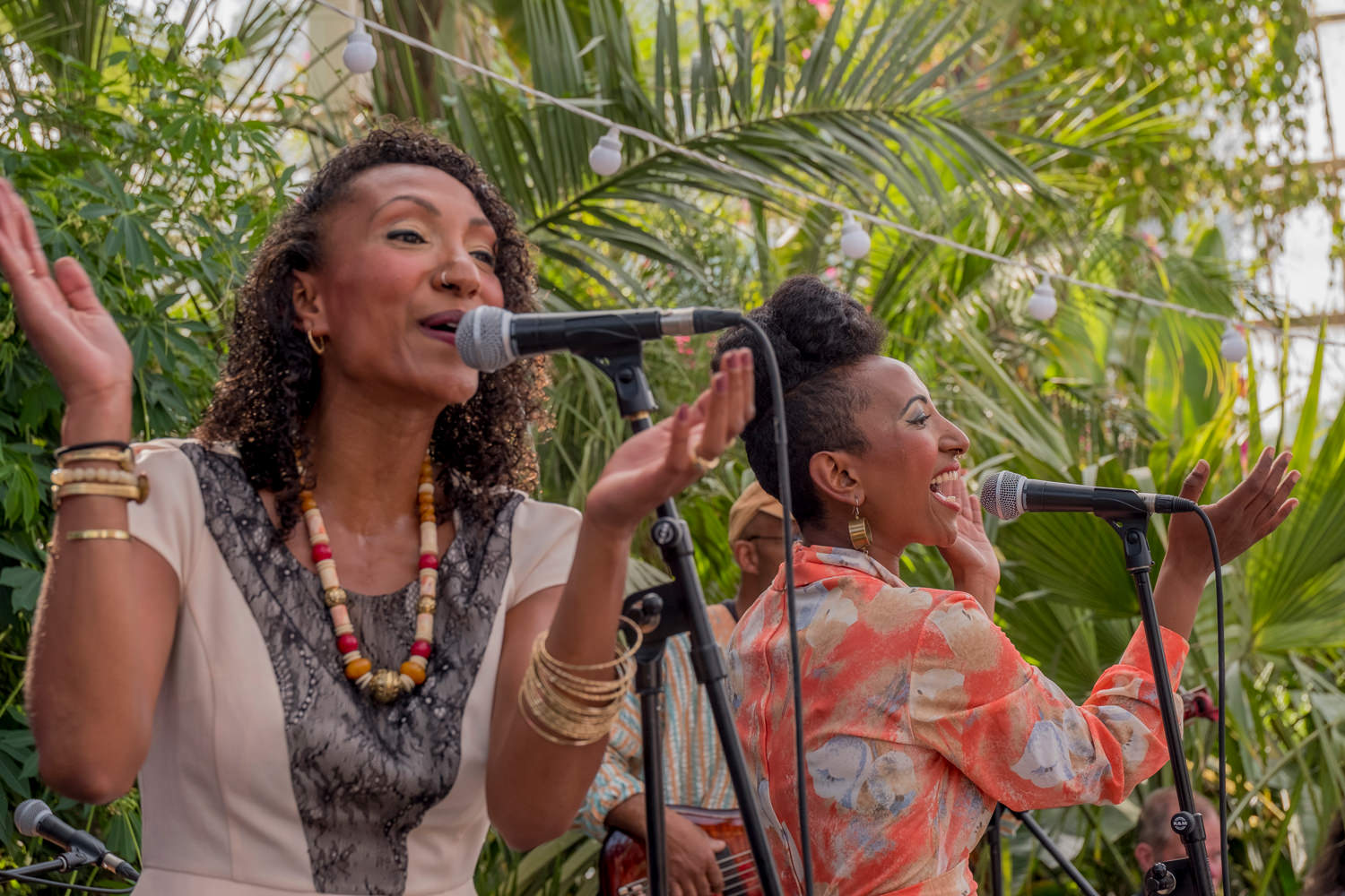 Two women standing next to each other, singing. They're clapping their hands and smiling as they sing.