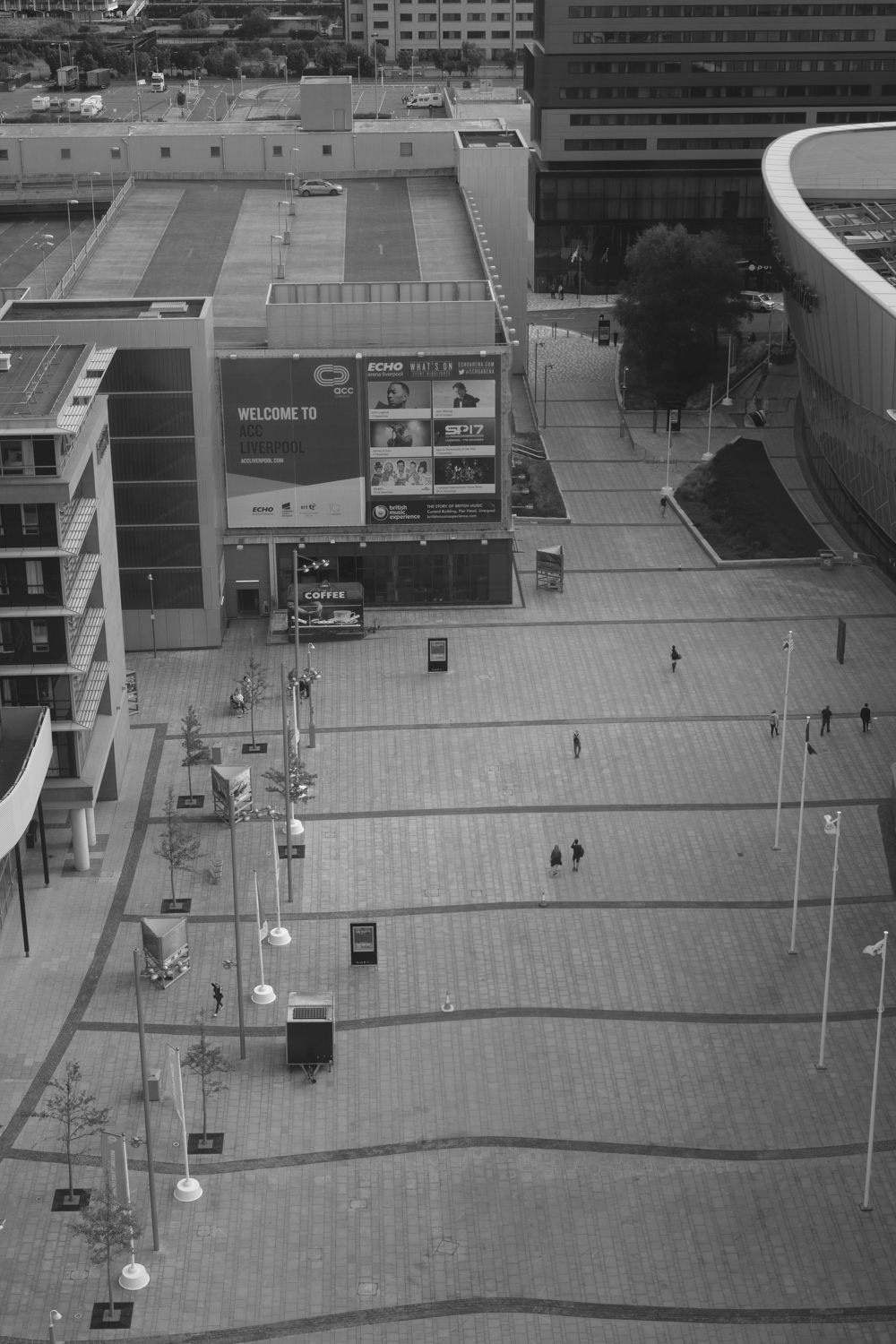 Looking down at a rectangular plaza in front of the Liverpool Echo Arena. Some people are walking along the plaza.
