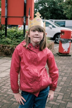 A girl posing with a burger king paper crown