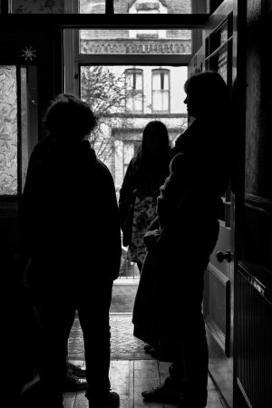 silhouettes of people standing by a front door, talking
