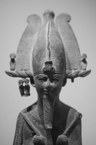 the top of a bronze statue of osiris