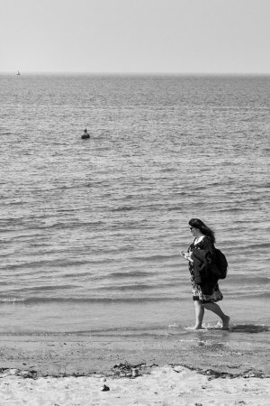 a woman walking along the edge of the sea on a beach