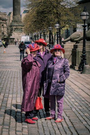 three ladies in purple coats and red hats