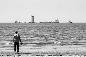 a man standing by the sea edge watching ships