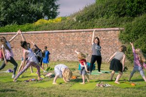 a woman taking a yoga class for children in a park